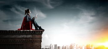 Super hero on roof. Mixed media. Thoughtful woman in cape sitting on top of building. Mixed media royalty free stock images