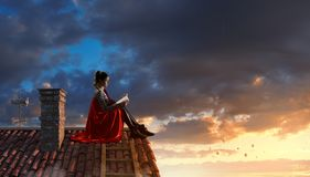 Super hero on roof. Mixed media. Thoughtful woman in cape sitting on top of building. Mixed media royalty free stock photography