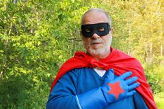 Super hero. Senior man super hero formal with a hand on heart Stock Images