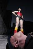 Super hero standing over the evil villain Royalty Free Stock Photo