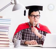 Super hero student wearing a mortarboard studying for exams