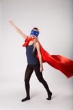 Super hero woman in superwoman costume. Young brave female raised her hand up stock image