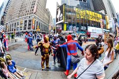 Super Heroes argue/fight Times Square New York City. People Dressed as super heroes Iron Man, Spider Man, Batman argue in front of passers by royalty free stock image