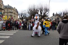 Super heroes parade in France. People are watching the super hero parade on the streets of Belfort city. Olaf and minions are walking next to each other. This royalty free stock image