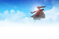 Super Heroine. Silhouette of a super heroine flying on clouds Royalty Free Stock Image