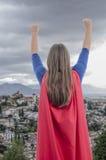 super héroe de la mujer con el cabo y los brazos rojos para arriba, fondo de la ciudad Foto de archivo libre de regalías