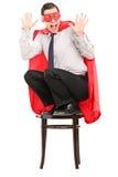 Super héros terrifié se tenant sur une chaise Images libres de droits