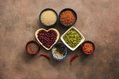 Super karmowi zboża, legumes, ziarna i chili pieprze na brązu tle, Chia, quinoa, fasole, gryka, soczewicy, sezam, zdjęcia stock