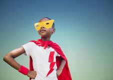 Super kid in red cape and yellow mask standing with hand on hip. Against turquoise background stock photo
