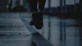 Super langzaam die motieclose-up van de voeten die van de vrouwelijke agent wordt geschoten op natte bestrating na regen lopen stock videobeelden