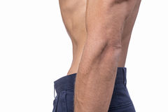 Super lean waist. Profile of torso of shirtless man wearing blue pants sucking in his thin waist on white background Royalty Free Stock Photos