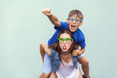 Super man style! The freckled brother climbed up on the back of a older cute sister. Making funny crazy face, tongue out and looki Royalty Free Stock Photography