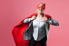 Super Manager, funny superhero. Female power, the girl in the mask of the hero and the red cloak,. Tearing jacket stock image