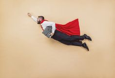 Super manager. Manager in a superman pose wearing a red cloak. Studio shot on a beige background stock photo