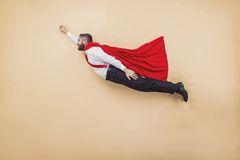 Super manager. Manager in a superman pose wearing a red cloak. Studio shot on a beige background royalty free stock image