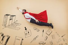 Super manager. Manager in a superman pose wearing a red cloak. Studio shot on a beige background Stock Images