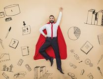 Super manager. Manager in a superman pose wearing a red cloak. Studio shot on a beige background Stock Image