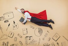 Super manager. Manager in a superman pose wearing a red cloak. Studio shot on a beige background Stock Photos