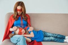 super matka patrzeje małego córki dosypianie na jej kolanach w masce i peleryna obraz royalty free