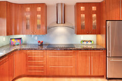 Super Modern Residential Kitchen. Modern kitchen, done with mid-century modern design with Asian accents. Includes cabinetry, granite counter, cook top, hood and Royalty Free Stock Photo