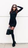 Super modna długonoga brunetki dziewczyna z długie włosy ubierającym w krótkiej czerni sukni, czarne szpilki z a Fotografia Stock