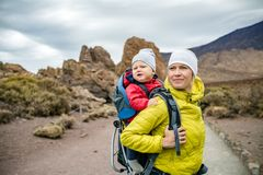 Super Mom with baby boy hiking in backpack. Super mom with baby boy travelling in backpack. Mother on hiking adventure with child, family trip in mountains Royalty Free Stock Photography