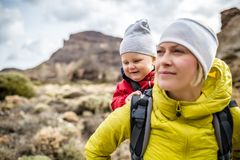 Super Mom with baby boy hiking in backpack royalty free stock photo