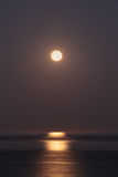 Super moon sets over the Pacific ocean Stock Image