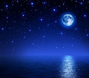 Super moon in starry sky on sea Stock Photos
