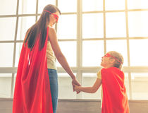 Super mother and daughter. Back view of mother and her little daughter dressed like superheroes holding hands, looking at each other and smiling, standing Stock Image