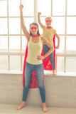 Super mother and daughter. Beautiful mother and her little daughter dressed like superheroes are keeping one hand up, looking at camera and smiling while playing Royalty Free Stock Photos