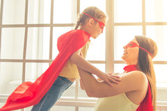 Super mother and daughter. Beautiful mother and her little daughter dressed like superheroes are looking at each other and smiling while playing at home Royalty Free Stock Image
