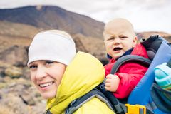 Super mother hiking with baby travelling in backpack Royalty Free Stock Photo