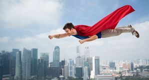 Man in red superhero cape flying in air over city royalty free stock images