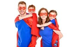 super rodzice piggybacking szczęśliwych dzieciaków w maskach i pelerynach zdjęcia royalty free