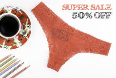 Super Sale. Red women`s panties and a coffee cup on a white back Royalty Free Stock Images