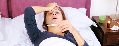 Super sick woman in bed checking temperature retro style Royalty Free Stock Images
