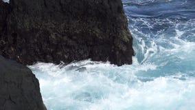 Super slow motion of eddy near volcanic rocks stock video footage