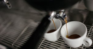 Super slow motion of hot espresso coffee pouring into a two white porcelain cups from coffee machine in 4k. ( top view close up&#x29 stock video footage