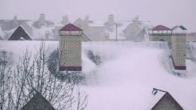Super slow motion pan shot of snowstorm above sloped roofs of residential houses in winter. Super slow motion video of snowstorm above sloped roofs of stock footage