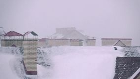 Super slow motion pan video of snowstorm above residential houses in winter. Super slow motion pan shot of snowstorm above residential houses in winter stock video