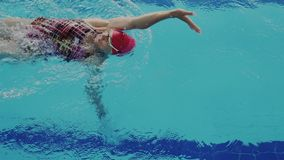 Super slow motion or rapid high speed footage. Top view of skillful female swimmer while she swims backstroke style in. The pool. Fitness and physical recovery stock video footage
