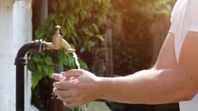Super slow motion shot of exterior tap water dripping and splash on a hot summer day stock footage