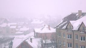 Super slow motion shot of snowstorm above sloped roofs of residential houses in winter. Super slow motion video of snowstorm above sloped roofs of residential stock footage