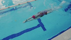 Super slow motion or rapid high speed footage. Top view of skillful female swimmer while she swims backstroke style in. Super slow motion. Top view of skillful stock footage