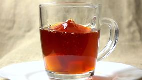 Super slow motion video of two sugar cubes falling into glass cup of black tea stock video footage
