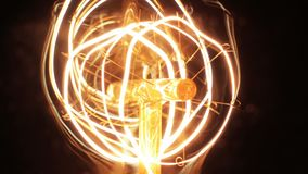 Super Slow Motion Vintage Lamp Light Bulb Close Up. Static close up super slow motion shot of the details within a carbon filament lamp while being swithed on stock footage