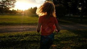 Super slow motion - a woman is jogging on the grass against the backdrop of sunlight stock video footage