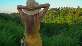 Super slowmotion shot of a young woman in a yellow dress walking during sunset at the Campuhan ridge walk or painter`s stock video