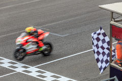 Super sport motorcycle crossing the finish line. Finish line and checkered race flag in hand royalty free stock images